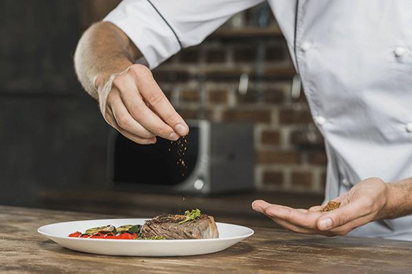 Chef cucina tagliata di carne